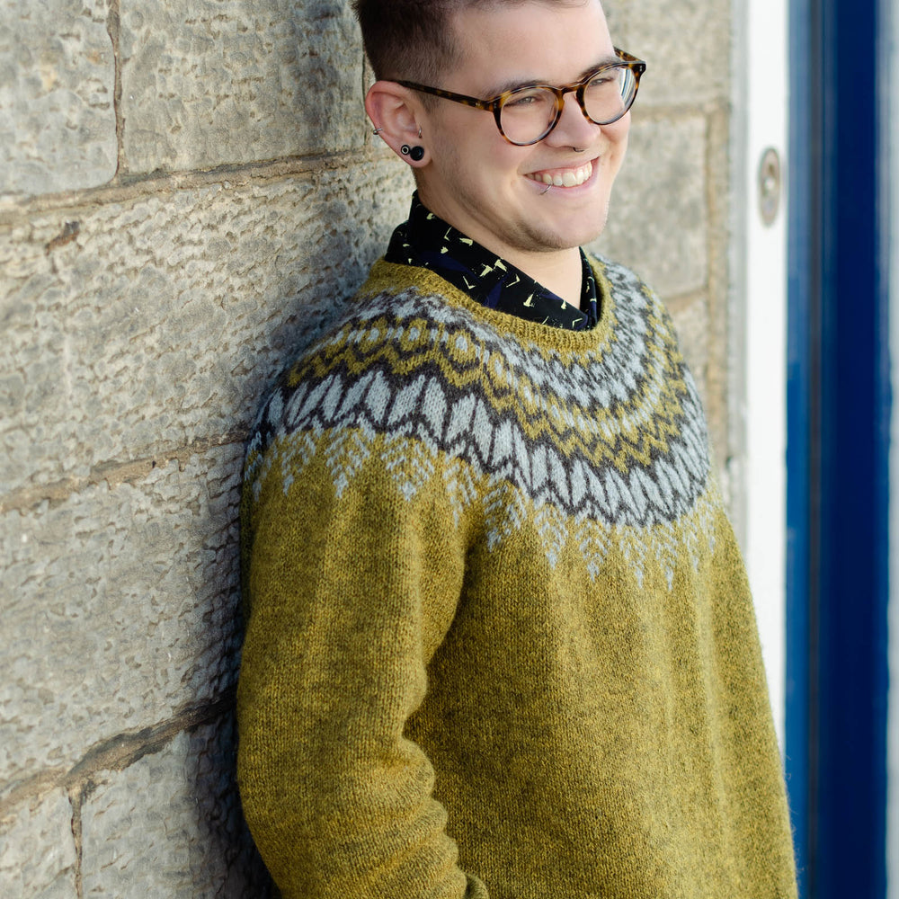 A white trans man leans casually against a light coloured stone wall, he has short hair, is wearing dark glasses and smiles at the camera. He is wearing an earthy green knit sweater with a dark brown and light grey colourwork yoke.