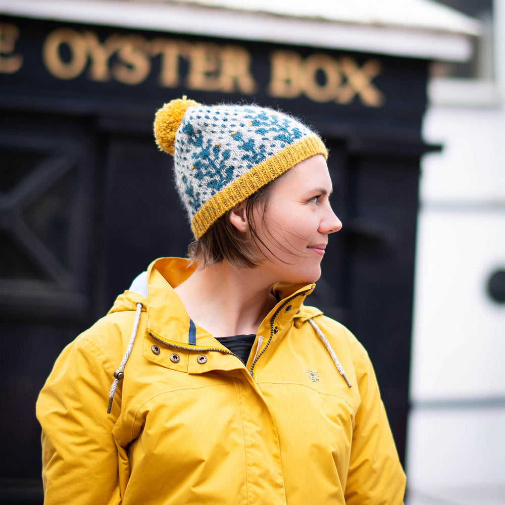 A white woman stands facing  to the right of the frame in front of a black painted restaurant front with gold letters 'Oyster Bar'.. The are wearing a yellow hooded jacket with the hood down and wearing a bold grey background and blue geometric botanic wool hat with yellow trim and pompom.