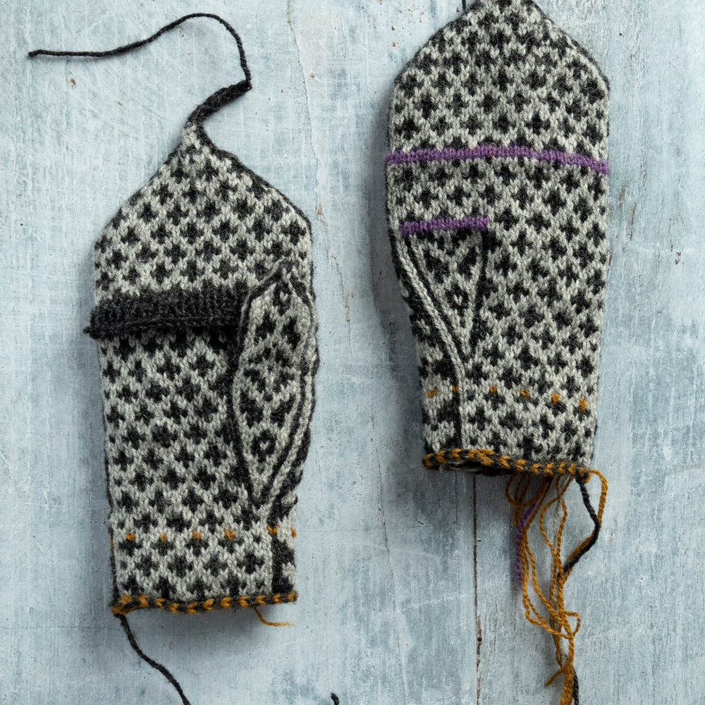 Broughton mittens in grey and black stranded colourwork, laying flat on a grey wood surface