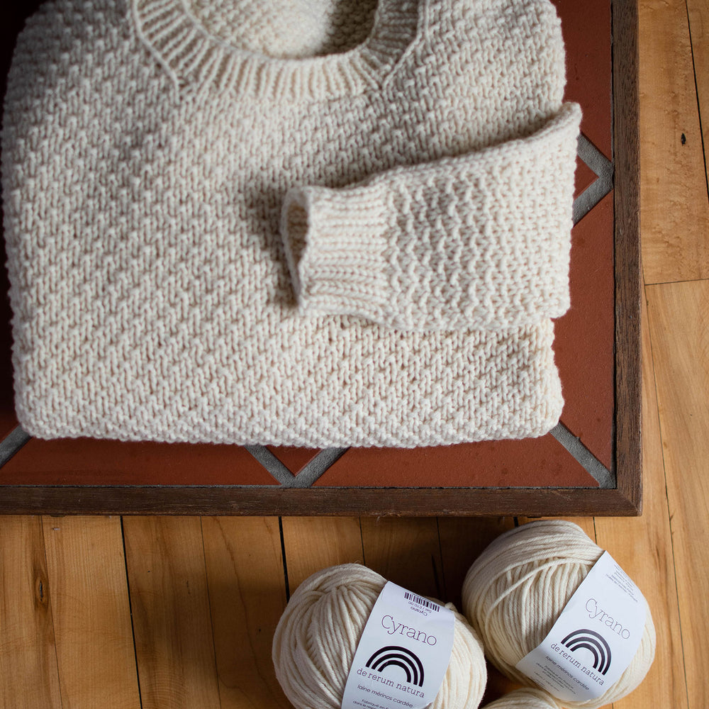 Overhead shot of a folded cream coloured textured knit jumper, there a balls of yarn in the same colour scattered in the bottom right of the shot.
