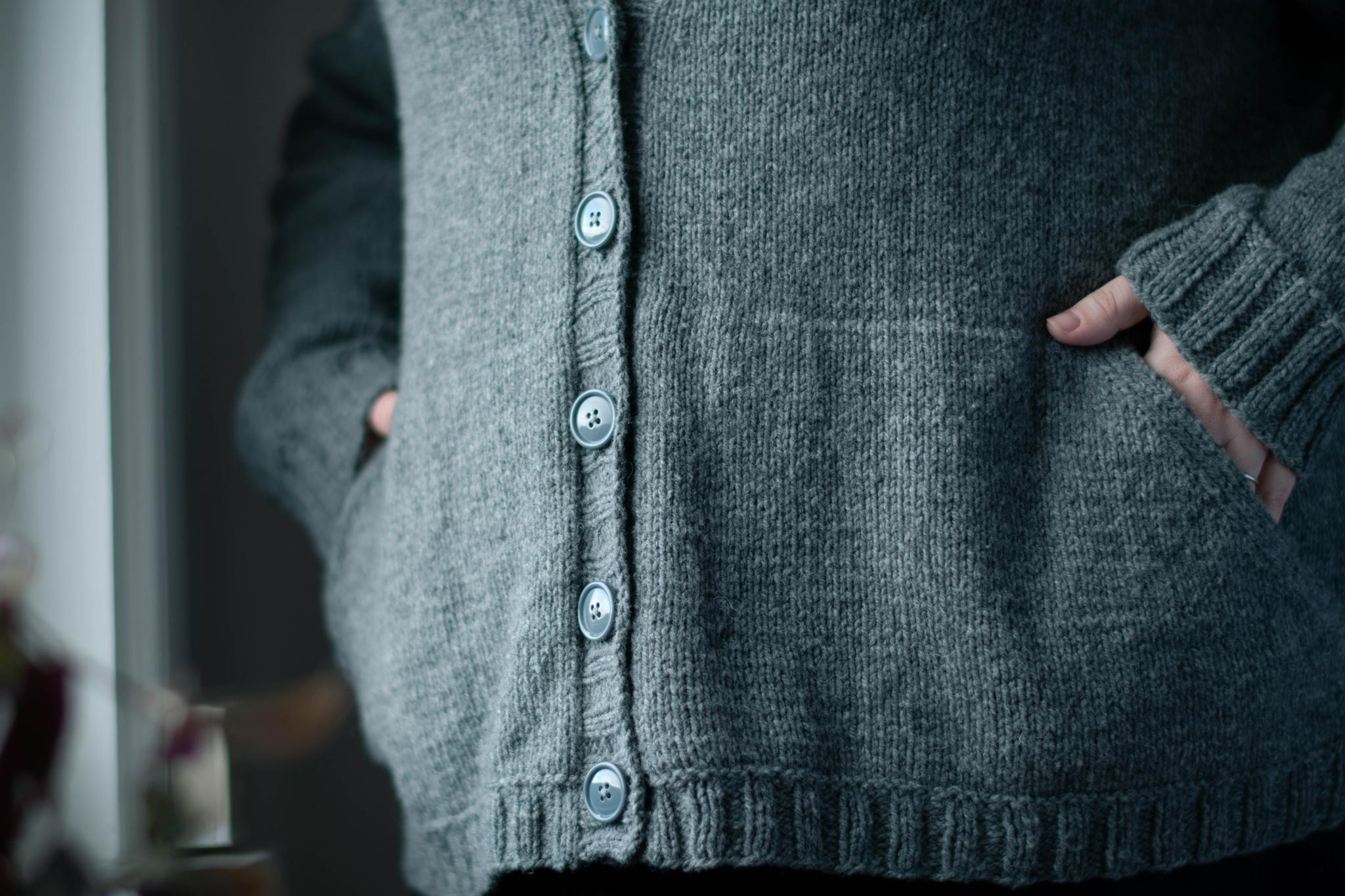 Image of the buttoned front of a grey cardigan, angled toward the light from a window. White-skinned hands are tucked into the angled pockeds.