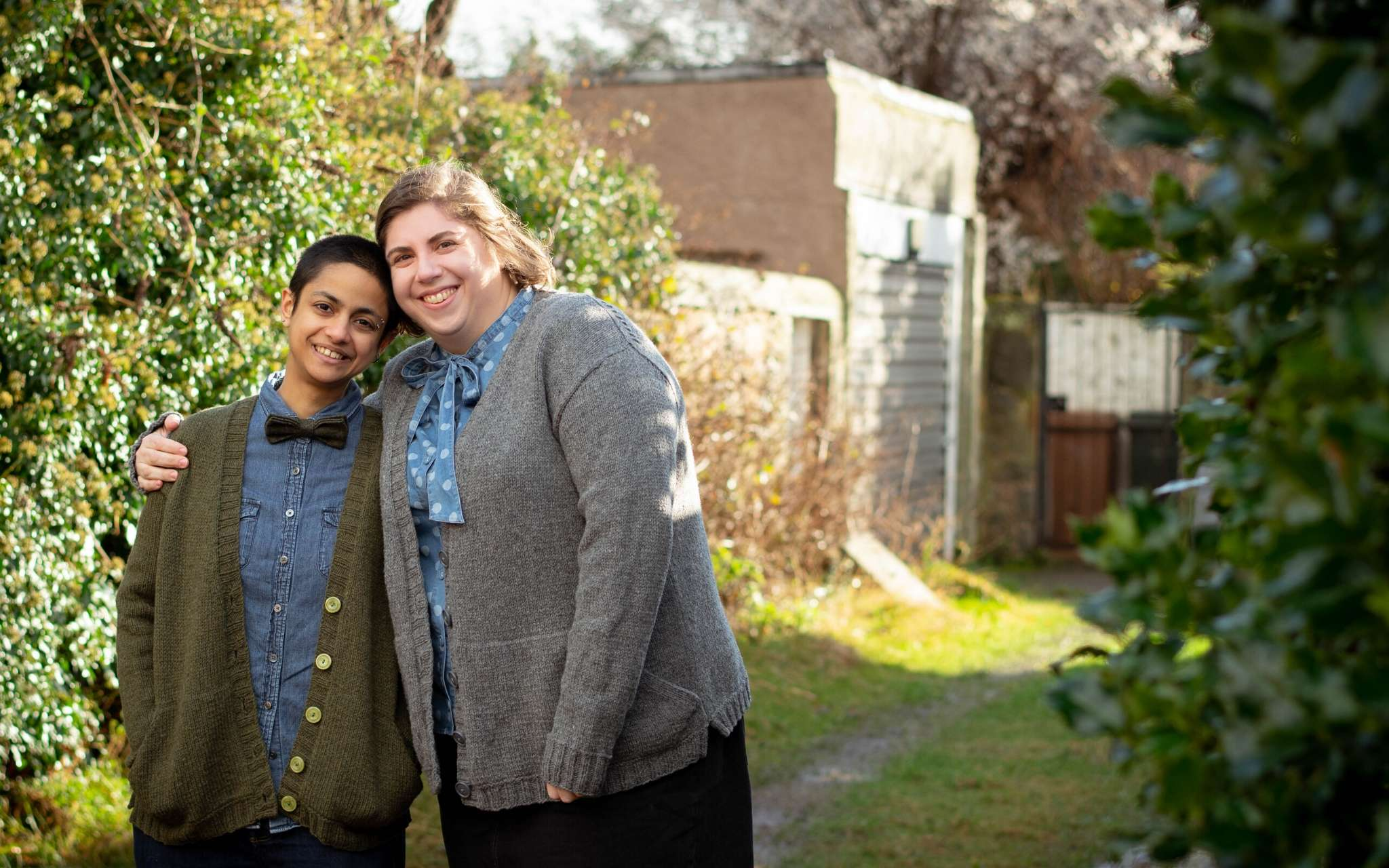 Two people stand hugging, both facing the camera, wearing granton cardigans in green and grey. One of them has brown skin and buzzcut dark hair, the other has white skin and a brown bob. They're both grinning.