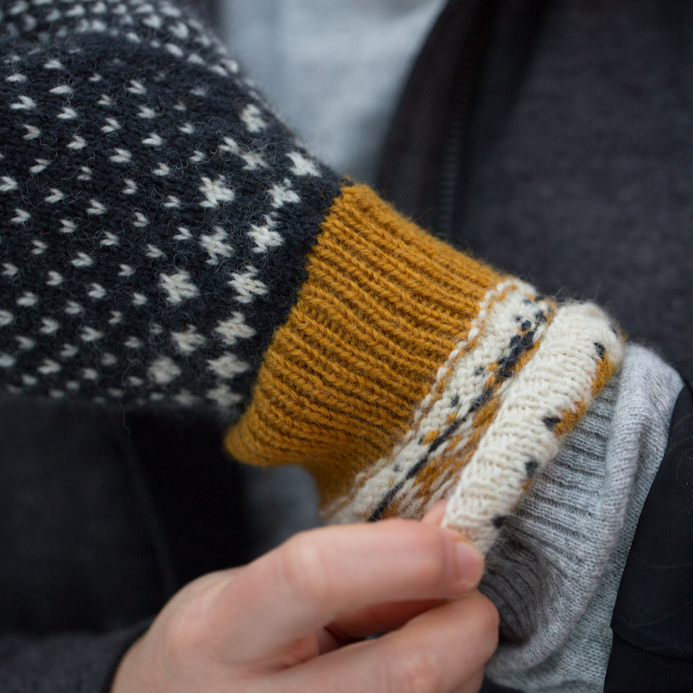 Close up shot of gold rib cuff of woollen colourwork knit mittens that is normally hidden by the decorative white with gold star cuff. The main hand of the mitten is navy blue mitten with white flecks.