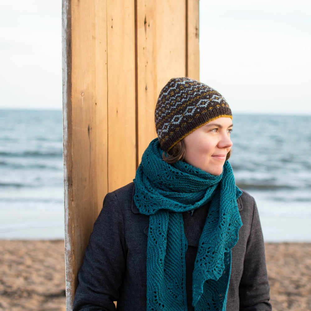 A white woman stands in front of a door on a beach. She's wearing a grey winter jacket, large turquoise wool shawl wrapped around her neck, and a fair isle beanie. The beanie is a chocolate brown base with light blue and gold motifs.