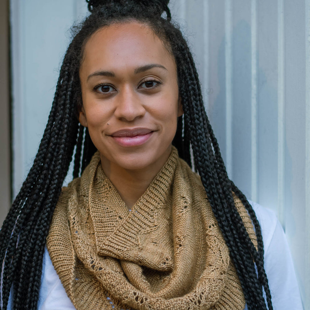 A black woman with long braids, leans casually against a white wooden wall. She's wearing a caramel coloured knit cowl and a white t-shirt.