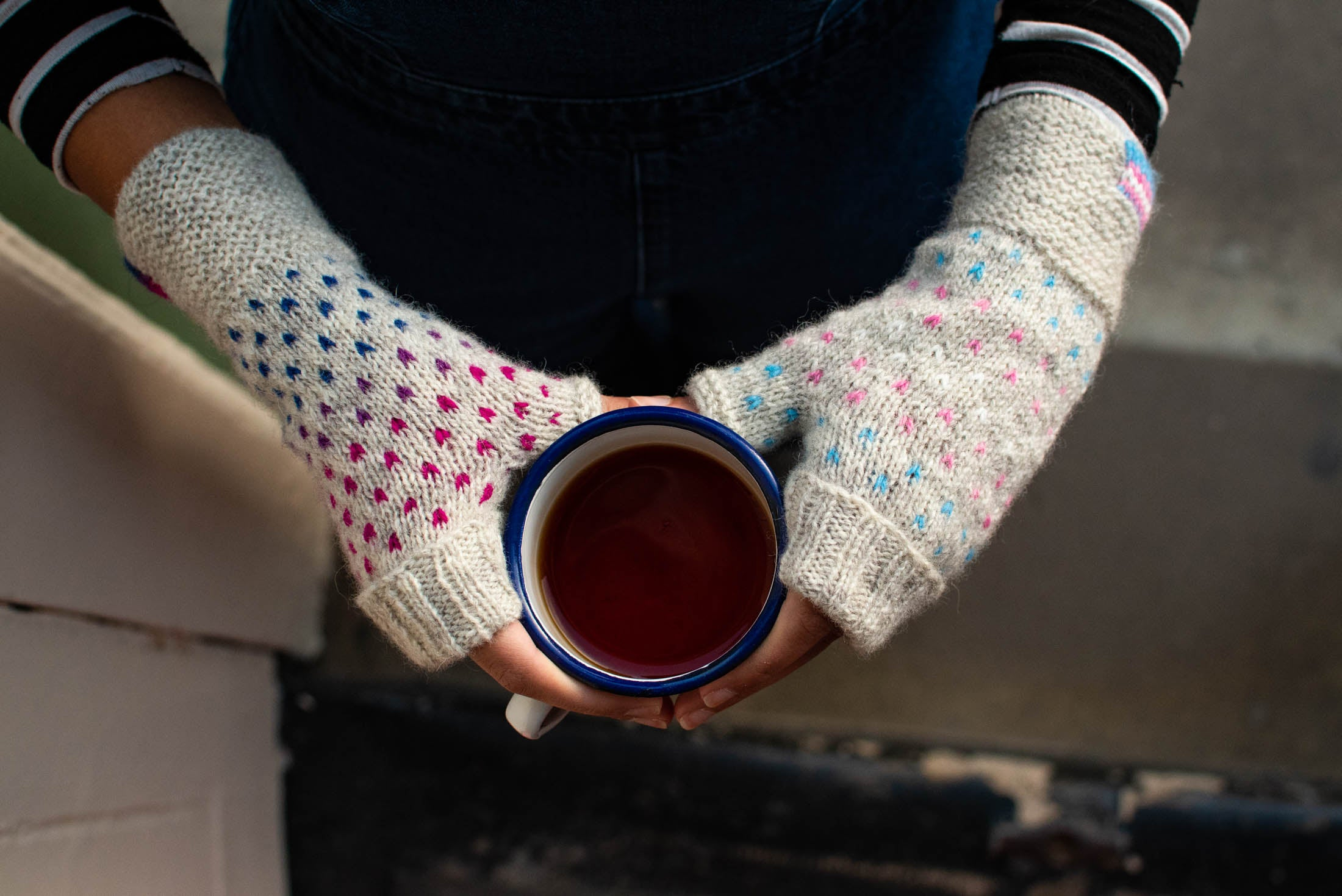 Image of hands shot from above, wearing a rainbow mitt and a bisexual mitt, holding a cup of black coffee