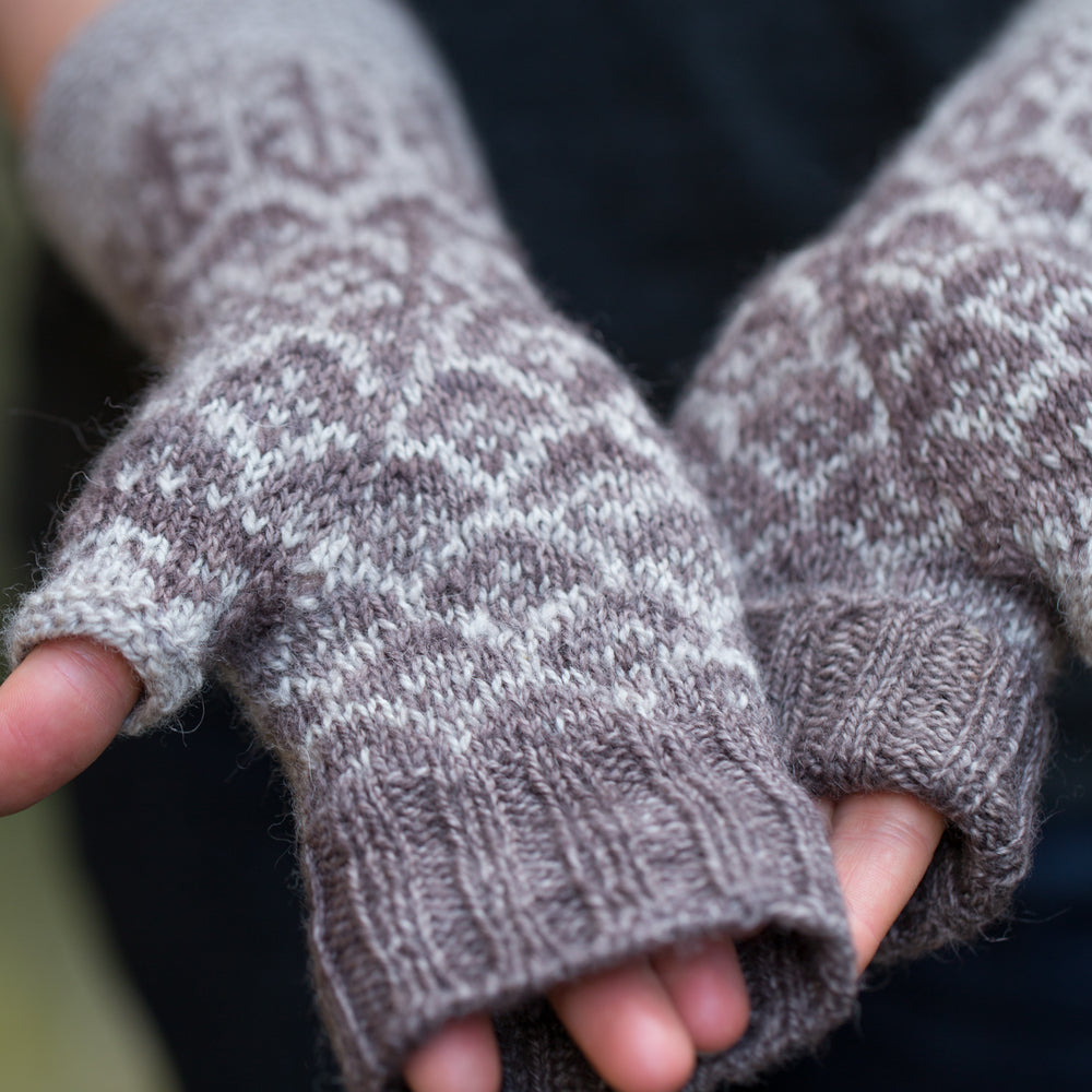 A person with white skin wearing the mitts, palms outstretched and showing that the ribbed cuff can be folded back or unfolded over the fingers