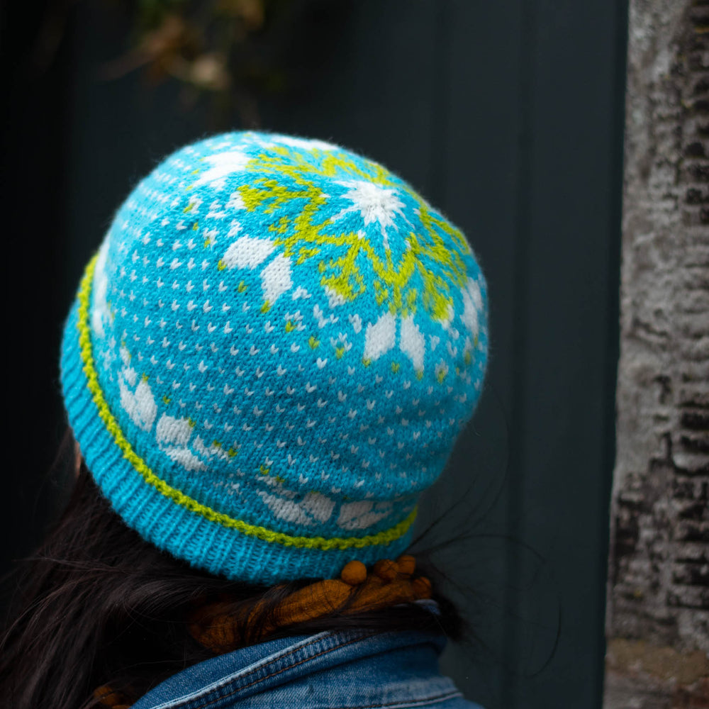 Person looks away from the camera, wearing a vibrant stranded colourwork hat with bold star motifs in bright blue, neon green, and white