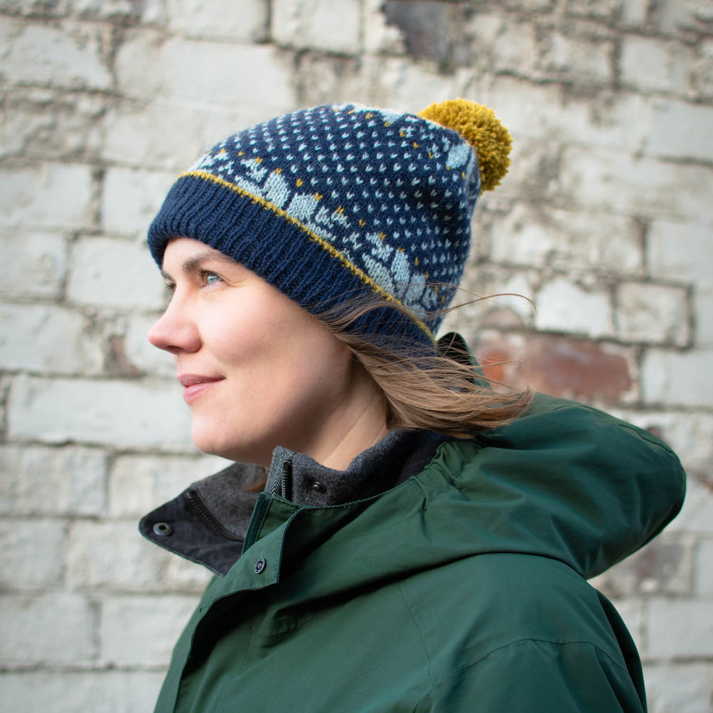 White woman with brown hair, wearing a green jacket and a dark blue, stranded colourwork hat with bold light blue star motifs and a yellow pom pom. She is standing in profile and smiling.