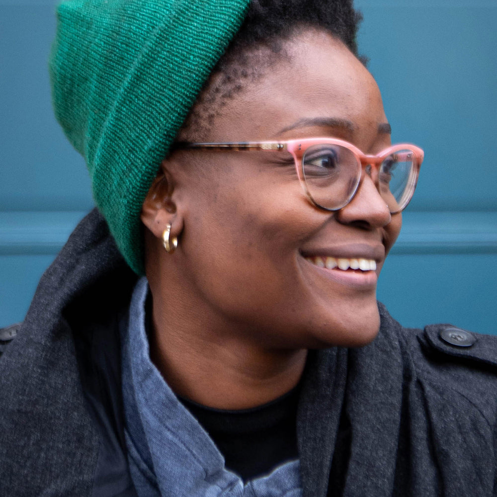A Black woman looks to the side smiling. She is wearing a green beanie hat with natural hair peeking out the front. She is wearing brown and pink glasses, a denim shirt, and dark grey coat