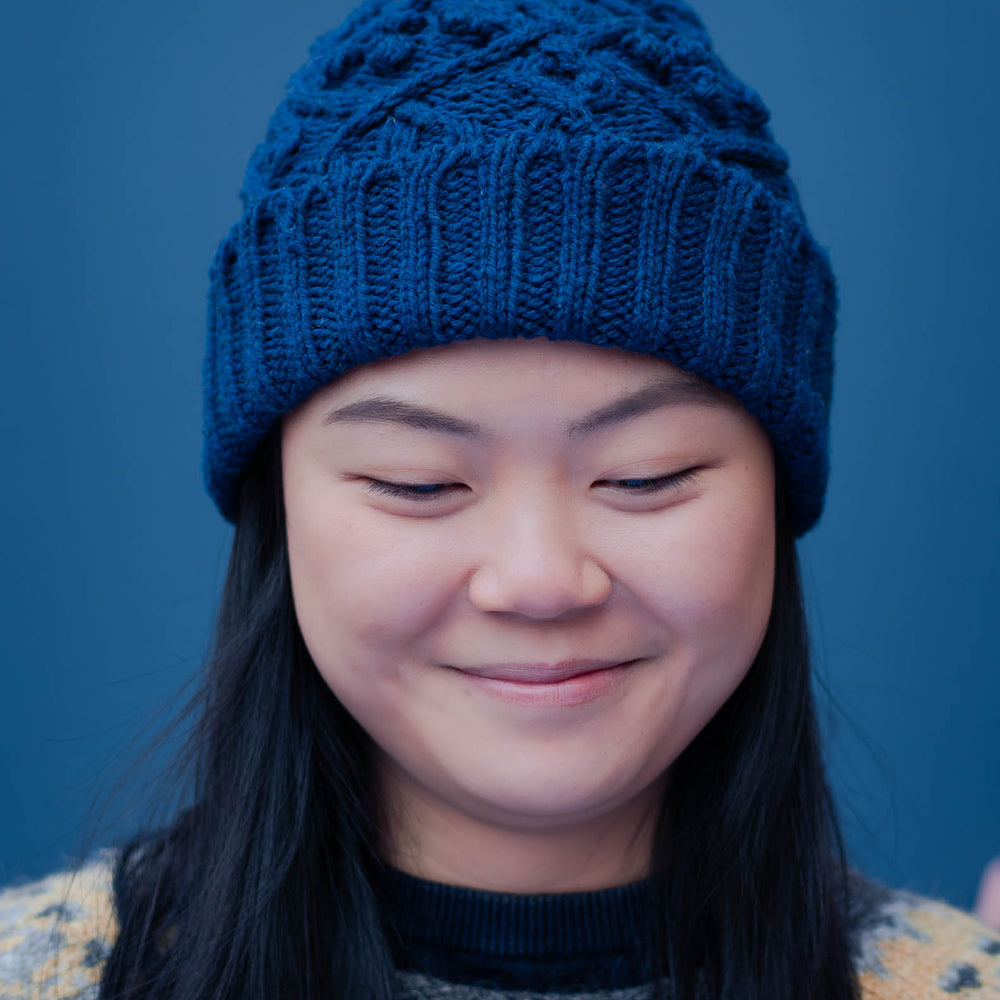Portrait image of a young asian woman wearing a blue cable beanie with a folded brim. She has long dark hair, that hangs down over the front a icelandic yoked sweater. The back ground of the image is blue.