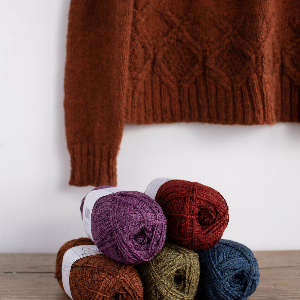 Lifestyle image of a pyramid of 5 balls of rich jewel toned yarn on a wooden surface. Hanging in the back ground you can see the bottom cabled hem of a burnt orange sweater against a white wall.