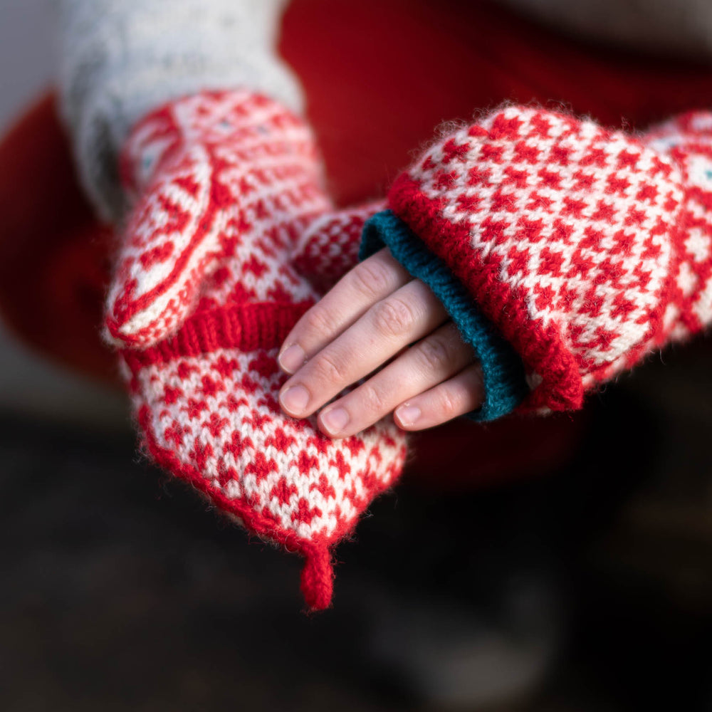 close up of two white hands with fingerless mittens on. mittens are bold red and white stranded colourwork. one flip top is closed, and one is open showing a blue knitted lining.