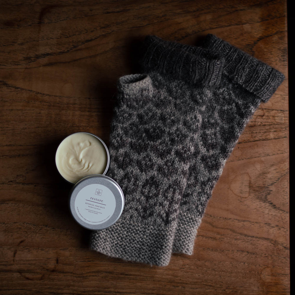 flat lay photo of brown mitts on a wooden table with an open tin of hand cream