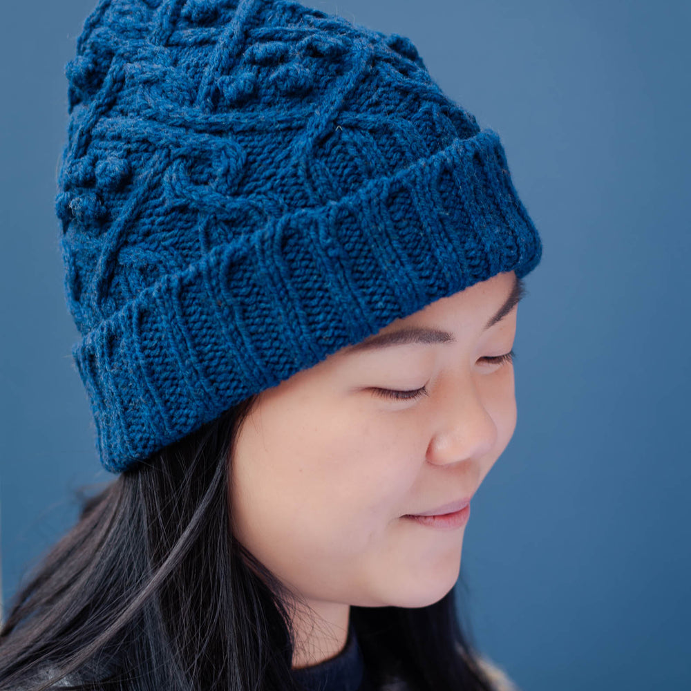 Profile image of a young asian woman wearing a blue cable beanie with a folded brim. She has long dark hair, that hangs down over the front an icelandic yoked sweater.