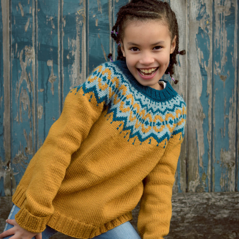 Child model wearing the Brunstane sweater in the vintage palette, in front a weathered wooden wall.
