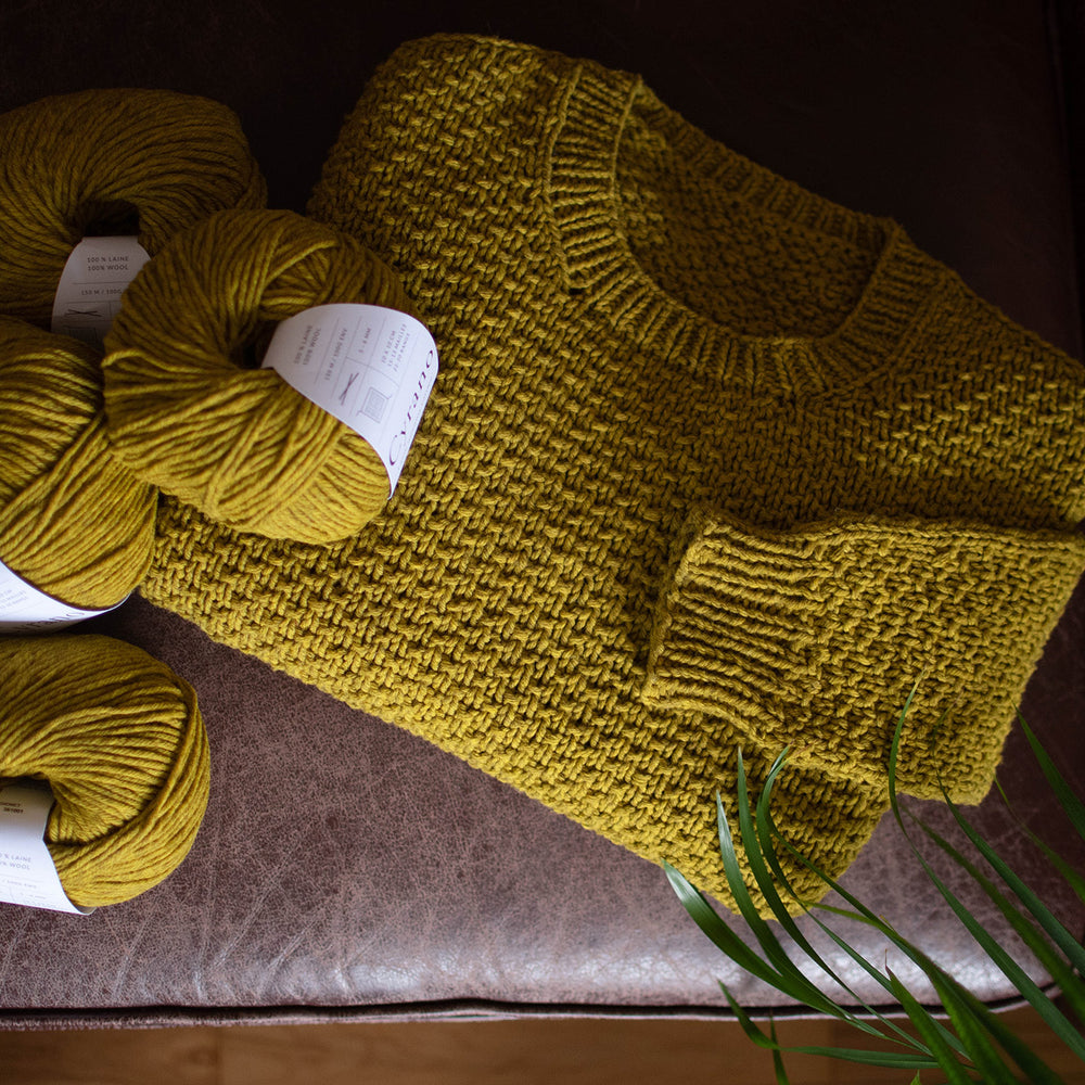 Moody overhead shoot of a mustard coloured textured jumper folded on a brown leather sofa. There are several balls of the same yarn scattered to the left of the shot.