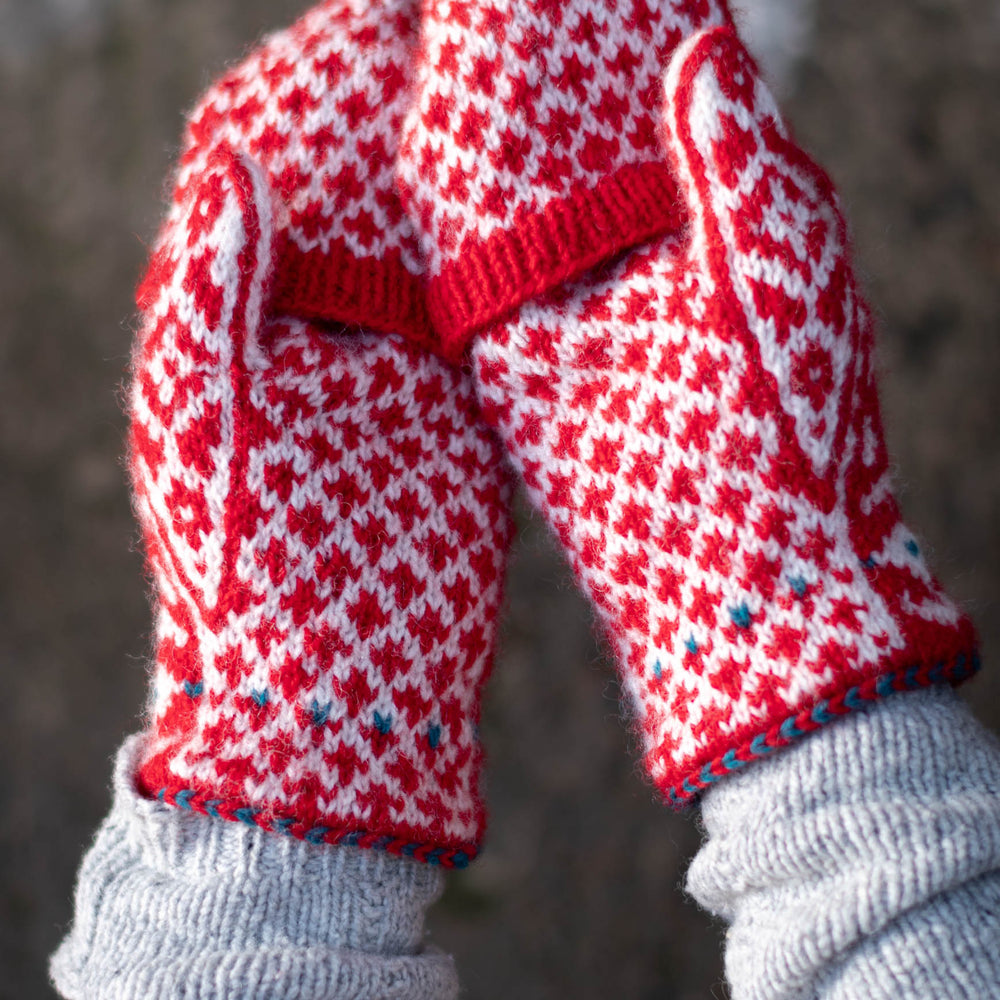 two hands, palms facing up, wearing red and white stranded colourwork mittens with a bold red and white diamond motif. the mittens have flip-tops