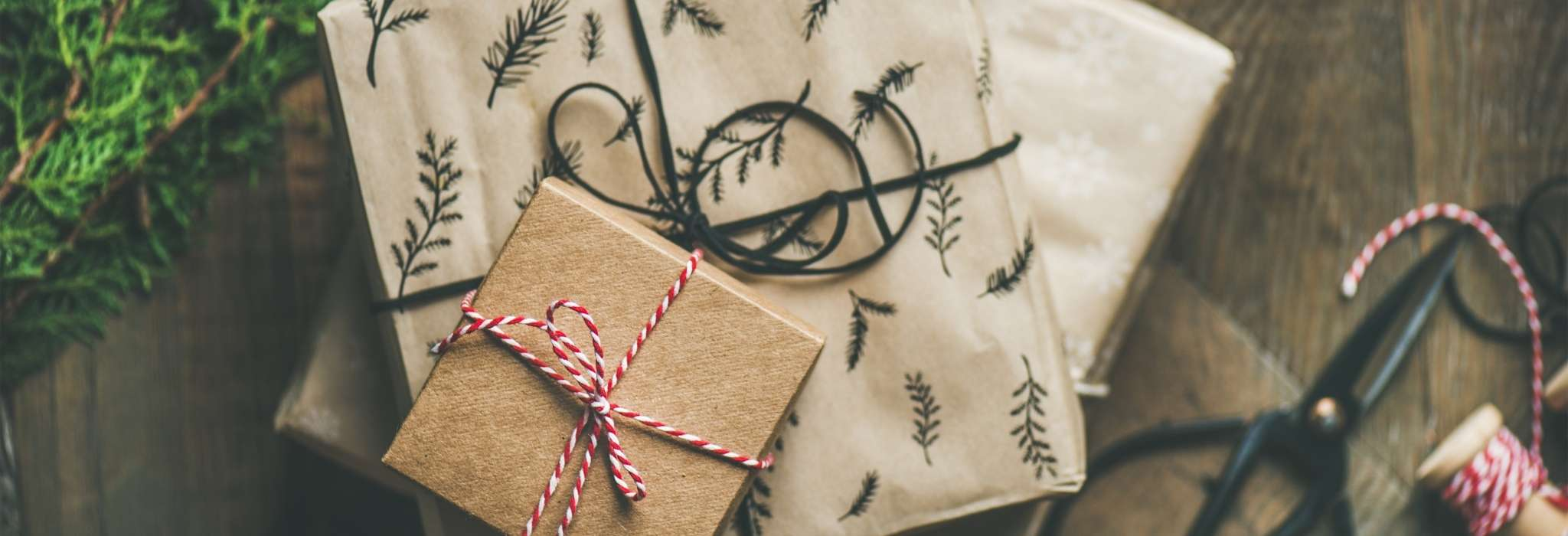 a pile of presents wrapped in brown paper and tied with red and white string are piled together on a wooden surface.