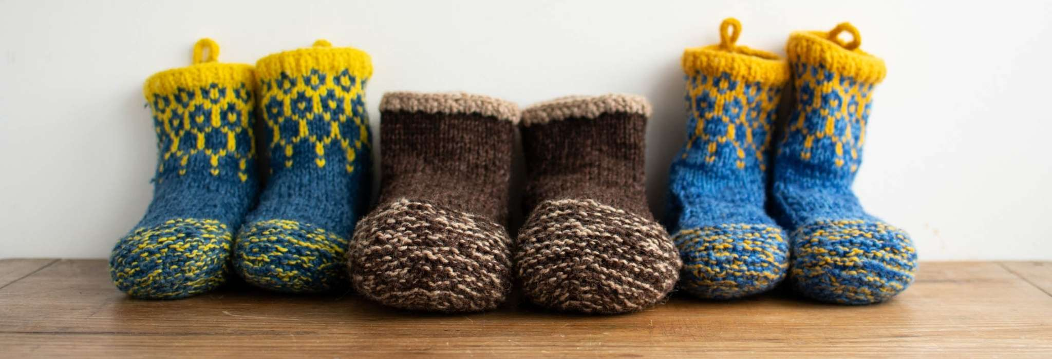 three pairs of knitted slippers lined up against a wall on a wooden surface. The pairs at either end are blue and yellow and the central pair are knitting in shades of brown.