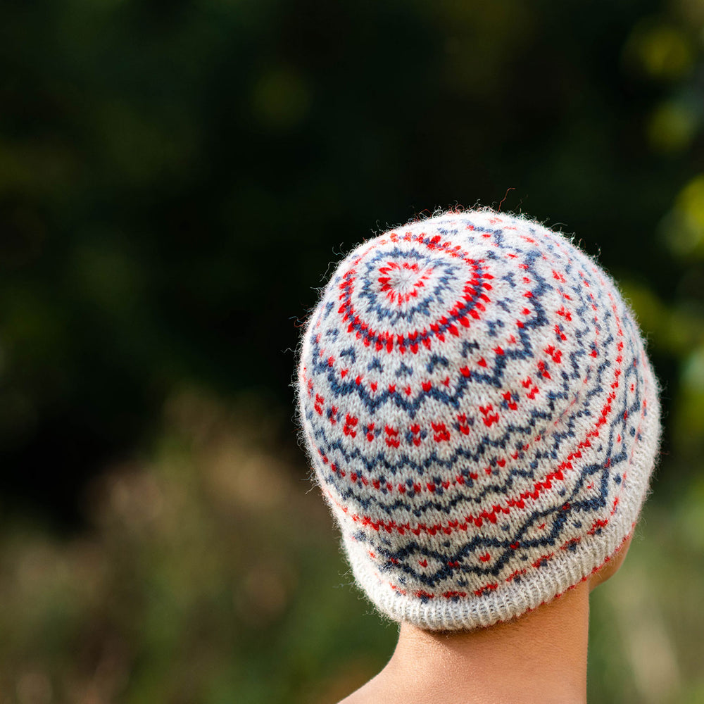 Close up shot of the back and crown view of a fair isle colourwork hat in a neutral base with red and blue motifs.