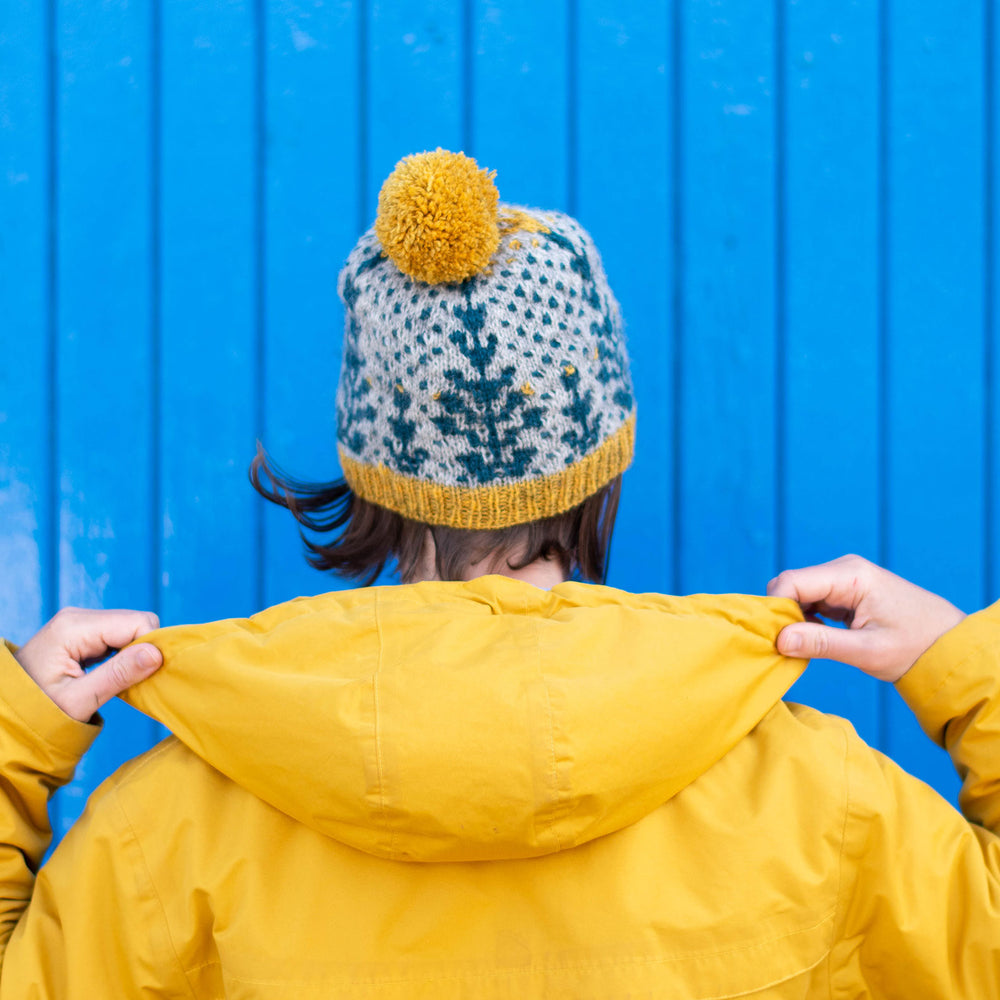 A person stands facing away from the camera towards a wooden slated wall painted blue. The are wearing a yellow hooded jacket with the hood down. They are holding the edges of the hood. They are wearing a bold grey background and blue geometric botanic wool hat with yellow trim and pompom.