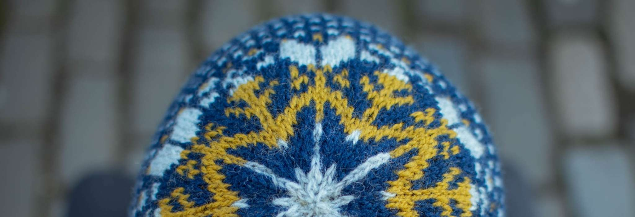 a close up of the crown of a blue, white and gold colourwork hat