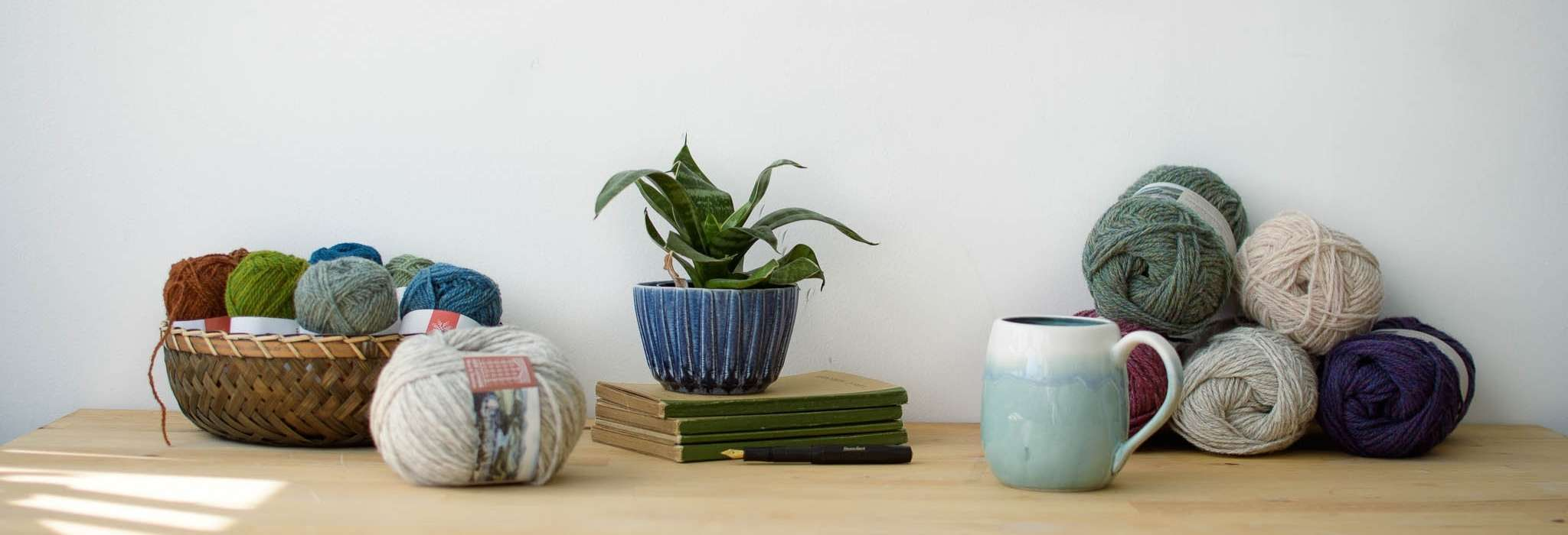 banner image shows a table with yarn, a plant and a mug