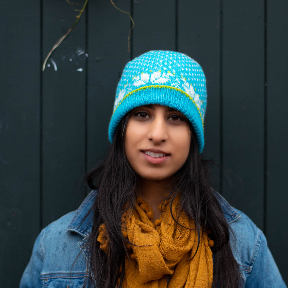 South Asian woman faces the camera smiling, she wears a bright blue stranded colourwork hat with bold star motifs, jean jacket, and yellow scarf.