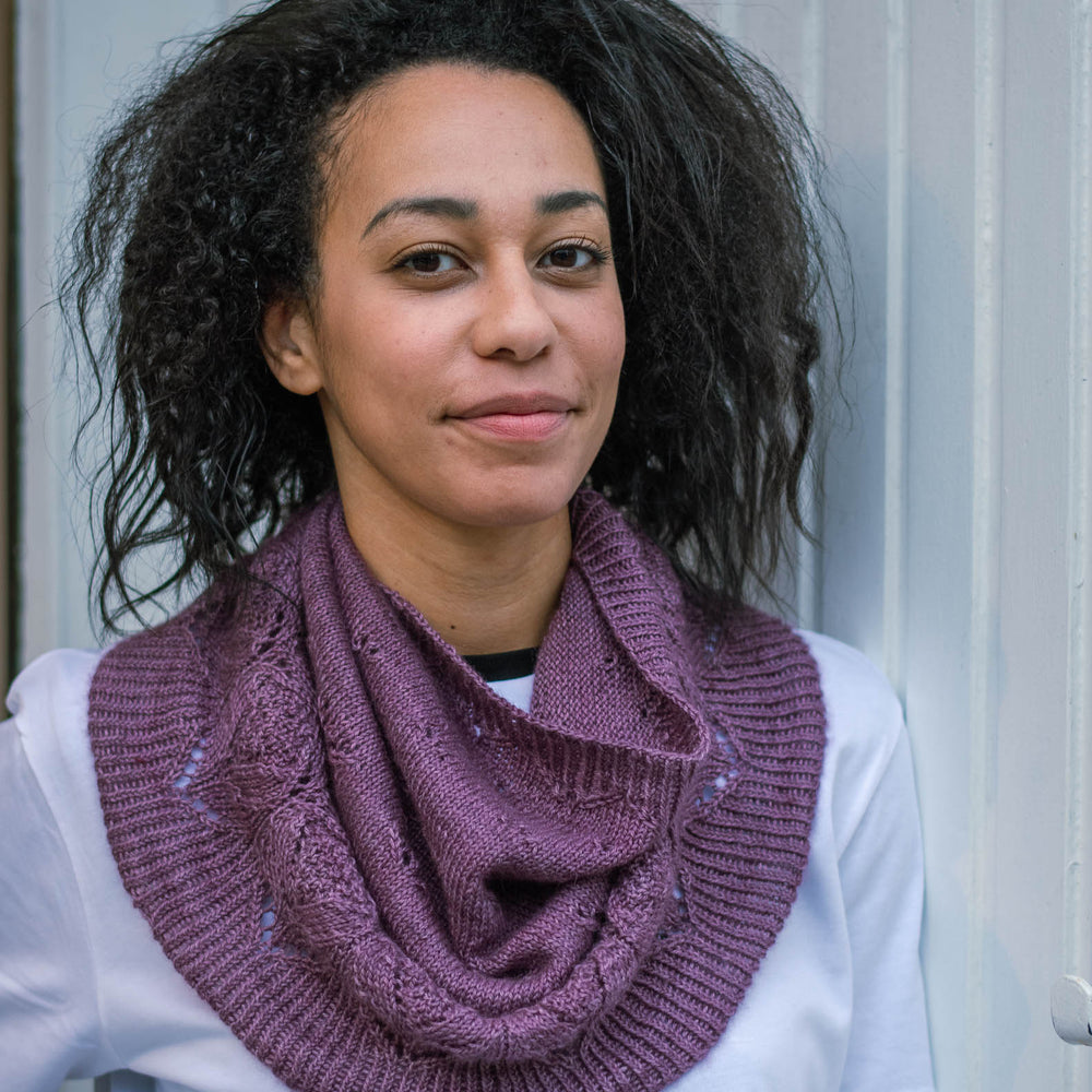 A black woman leans casually against a white wooden wall. She's wearing a deep purple knit cowl and a white t-shirt.