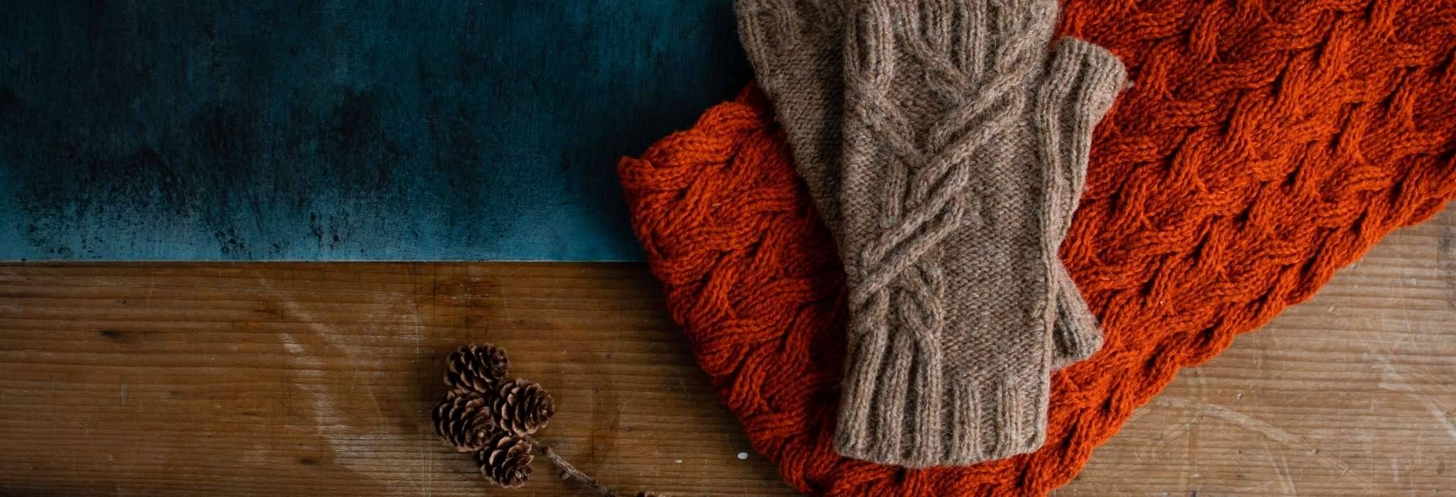 A deep orange cabled cowl lies flat on a wooden surface, slightly overlapping a folded piece of teal fabric. A pair of cabled brown fingerless mitts are arranged on top.