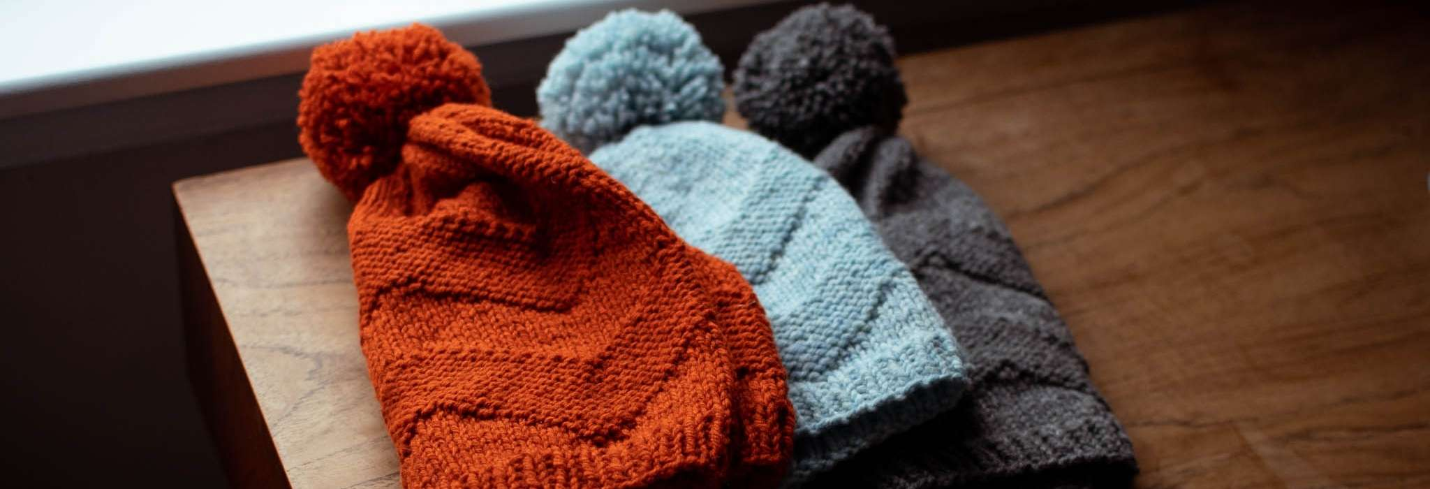 Three beanie hats in orange, blue and grey lie overlapping each other on a wooden table. They have pom poms and a chevron stitch pattern.
