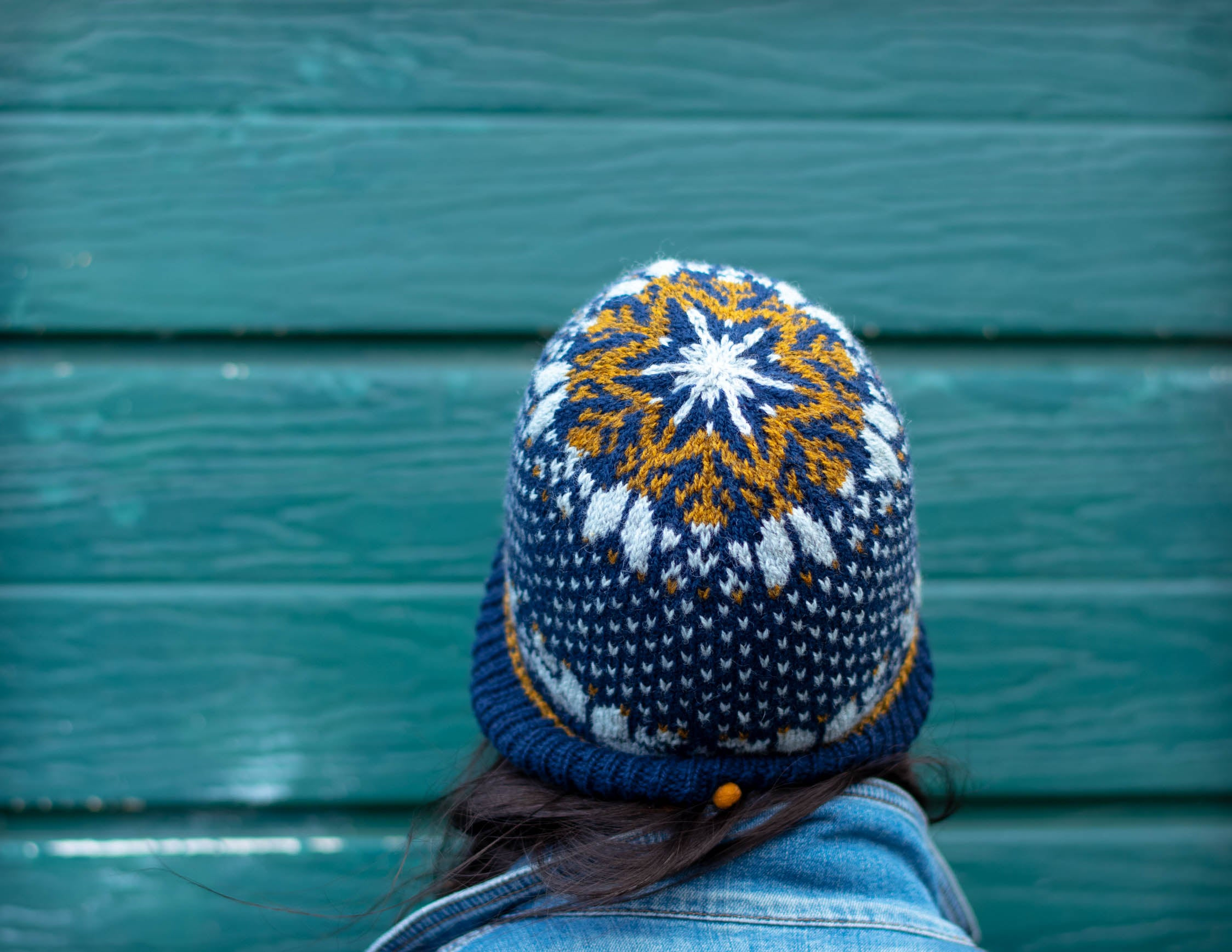Image of a person wearing stranded colourwork hat with snowflake on the crown, facing away from the camera, in front of a green wall.