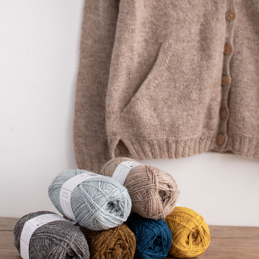 Product lifestyle image 6 balls of yarn in a pyramid sit on a wooden surface in front of a cardigan in a neutral colour with pockets hangs on the wall.