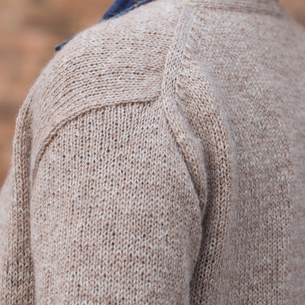 Close up image showing the English tailoring detail on a neutral coloured knit cardigan.