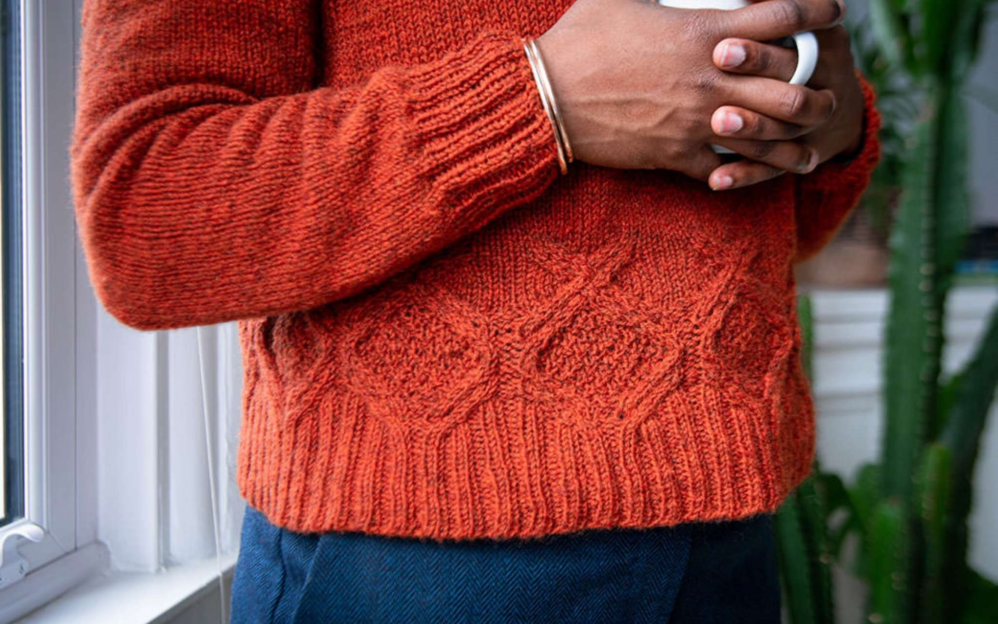 a close up of the bottom of a rich orange cabled sweater, worn by a black model holding a mug