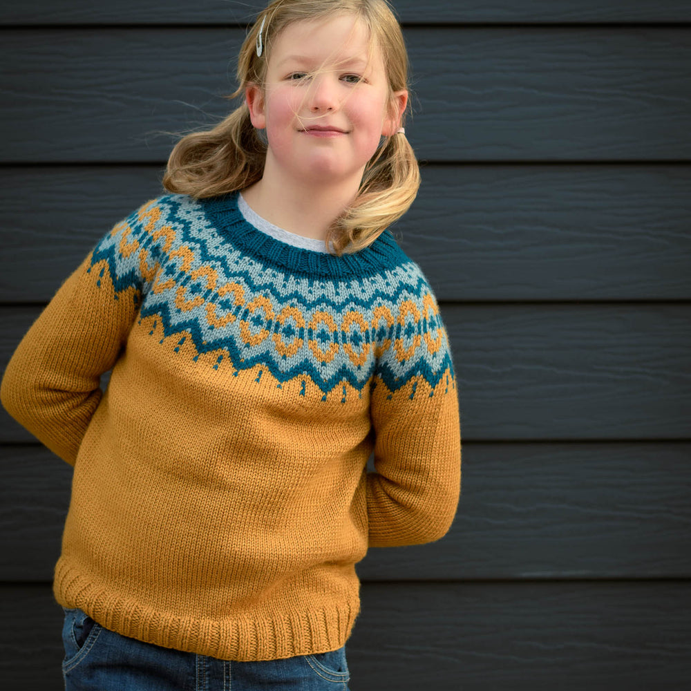 Blond child with pigtails, wearing the Brunstane Sweater in the vintage palette standing in front of a dark slated wall.