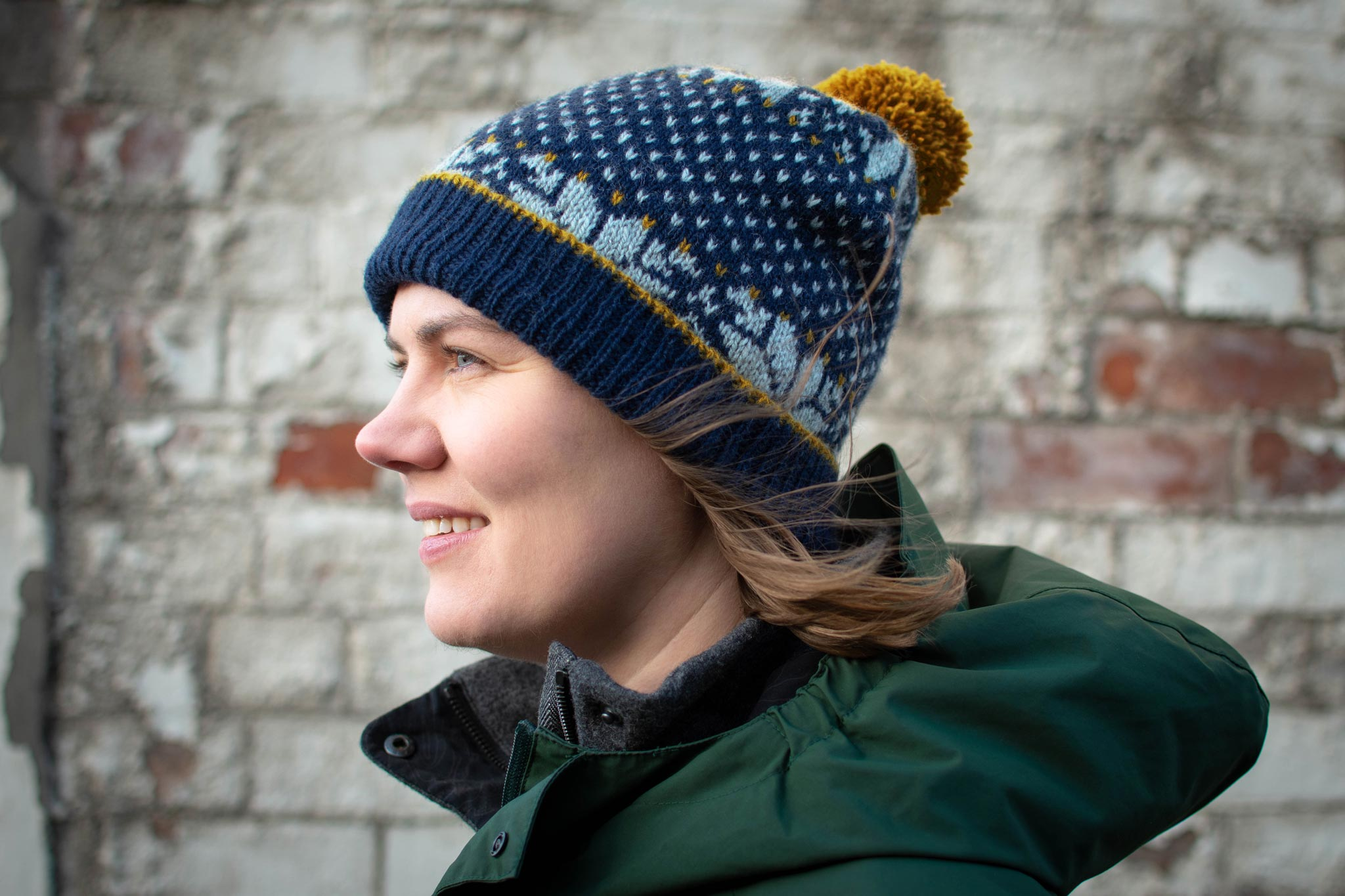 Image of Ysolda, a white woman, facing left and wearing a blue colourwork hat with a folded up brim and a gold pompom.