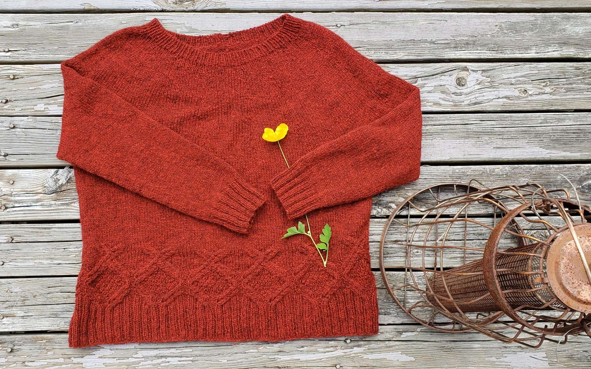 rich orange sweater with cabled hem, laying flat with a yellow flower