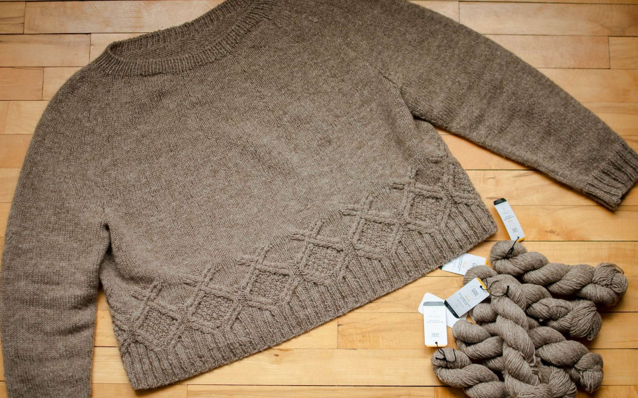 a pale brown neutral sweater with cabled detail around the hem is laid out flat on a wooden surface. Twisted skeins of the same yarn are piled next to it.