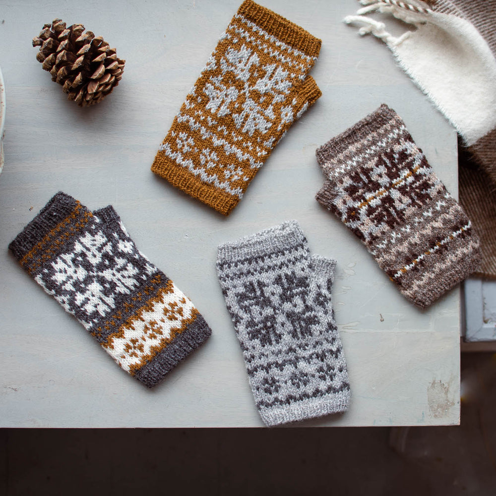 overhead view of 4 stranded colourwork mitts laying on a table. all of the mitts are in shades of brown, grey, and white.
