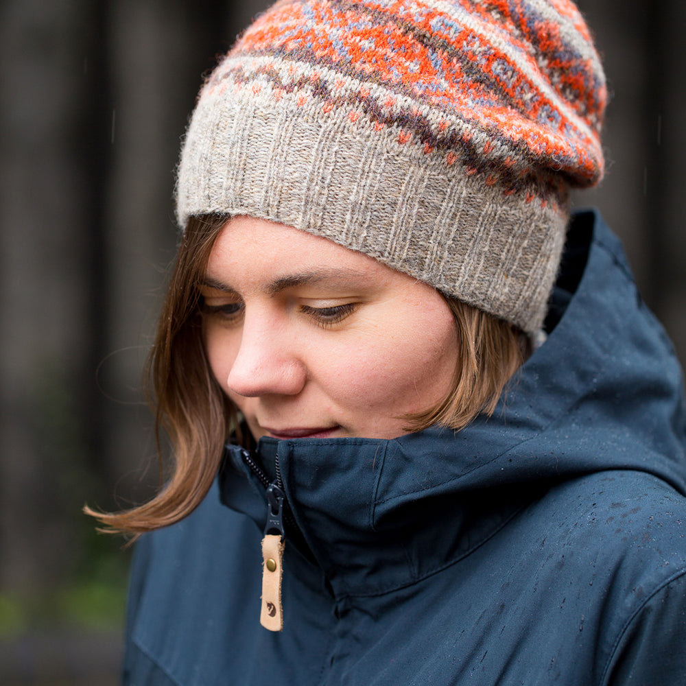 Ysolda, a white woman with chin-length brown hair, is huddled in a blue coat and is looking at the ground. She is wearing an orange and brown fair isle hat.