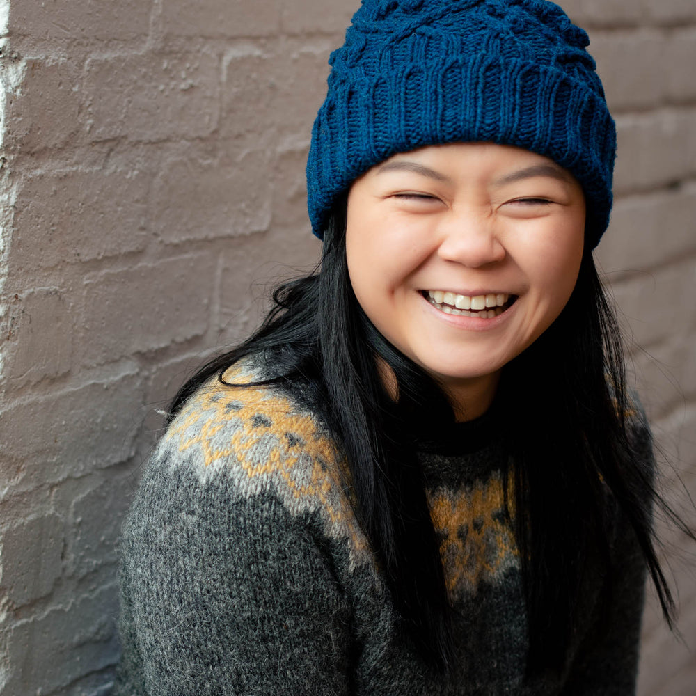 Portrait image of a young asian woman wearing a blue cable beanie with a folded brim. She has long dark hair, that hangs down over the front an icelandic yoked sweater. She's in front a white brick wall, she exudes joy.