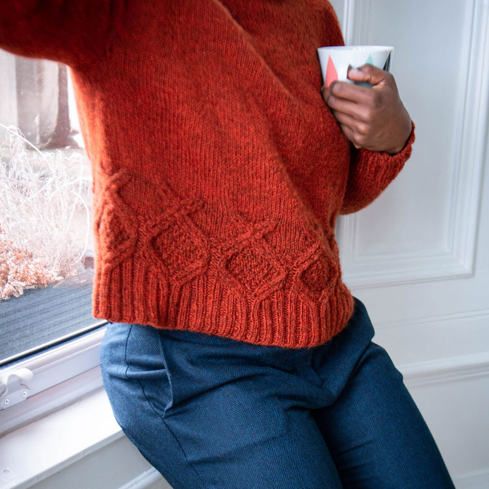 A person leans against a window sill. Wearing an orange wool sweater with cables above the ribbing, with dark blue trousers.