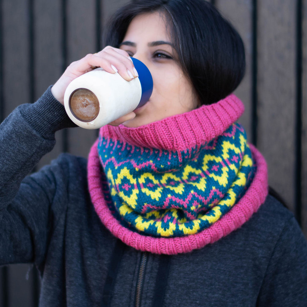 South Asian woman drinks from a reusable mug, she is wearing a stranded colourwork cowl in vibrant colours - neon yellow, neon pink, and deep blue