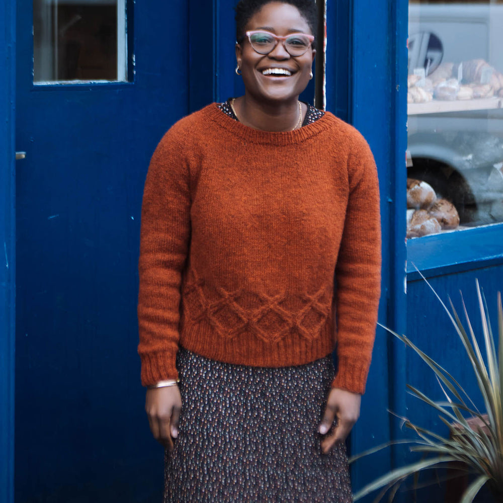 A black woman with short hair and glasses, stands in front of a doorway painted blue. She's laughing and facing the camera, wearing an orange wool sweater with a round yoke and cabled detail around the waist over a dark coloured mini floral print maxi dress.