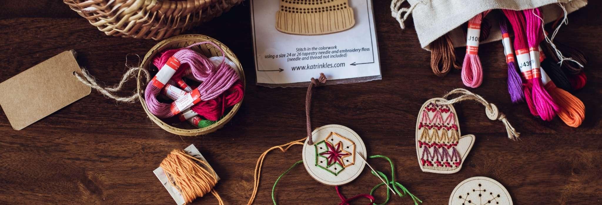 Wooden stitchable ornaments lie on a wooden surface, with stitching done in brightly coloured thread. A pile of threads and a wicker basket lie next to them.