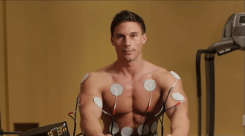 Man using tone-a-matic muscle stimulator to workout with pads on upper body