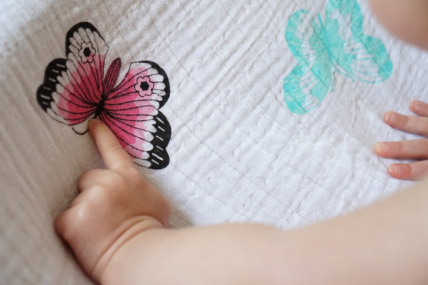 pointing to pink butterfly on the muslin swaddle