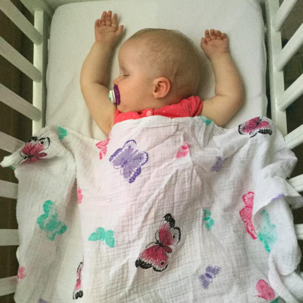 baby asleep with butterfly swaddle on top
